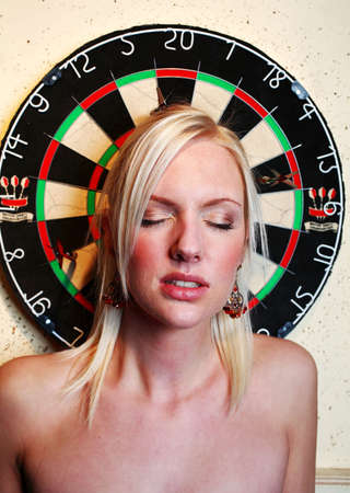 bare shoulders: Woman standing in front of dartboard, being the target