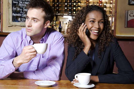 bar: Businesswoman talking on the mobile phone, man holding cup while looking away