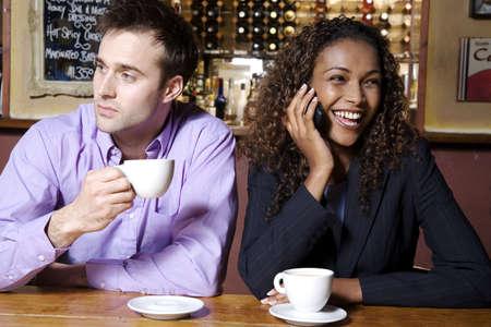 De negocios hablando por el tel�fono m�vil, el hombre celebraci�n taza mientras se mira lejos  LANG_EVOIMAGES
