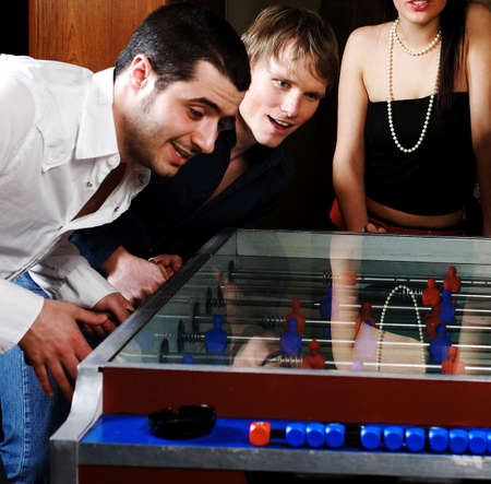 Men and woman playing foosball