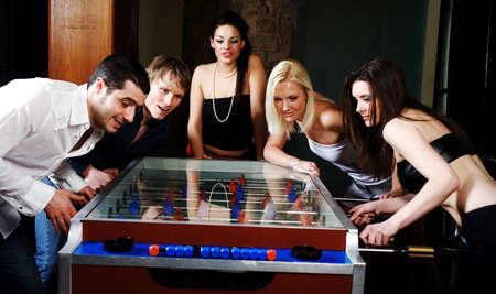 Los hombres y las mujeres jugando foosball