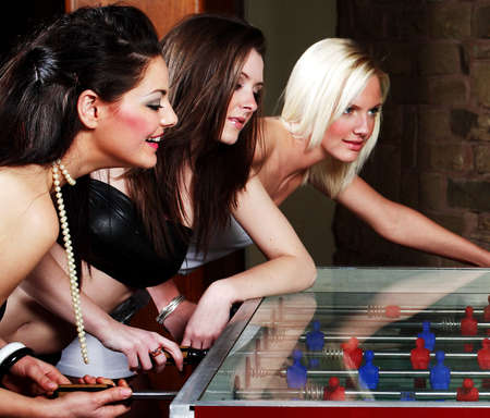 Women playing foosball