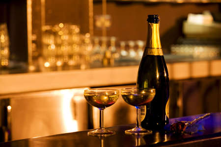A bottle and two glasses of champagne on the bar counter