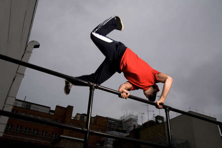 Man jumping over metal railing