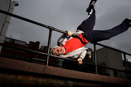 Man turning upside down while holding on to metal railing LANG_EVOIMAGES
