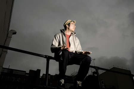 Hombre sentado en la barandilla, tocando en su regazo