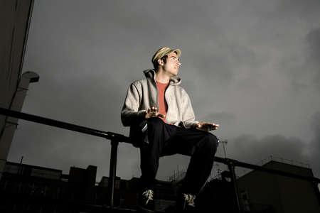 Man sitting on railing, tapping his lap