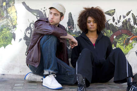 Man and woman leaning against graffiti wall
