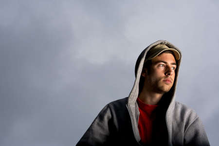 Man in hooded jacket looking away LANG_EVOIMAGES