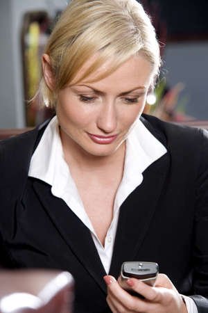 Businesswoman text messaging on mobile phone LANG_EVOIMAGES