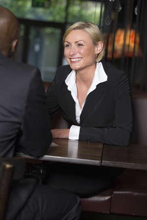 Businessman and businesswoman in a restaurant, focus on businesswoman