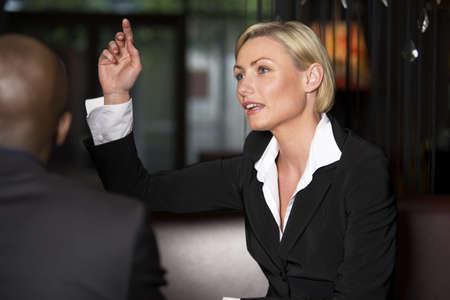 Businesswoman raising her hand to order food