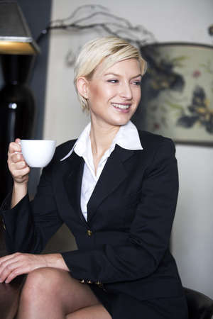 Businesswoman holding a cup of coffee LANG_EVOIMAGES