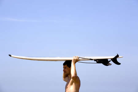 Man carrying surfboard on top of his head