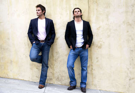 Two men leaning against the wall