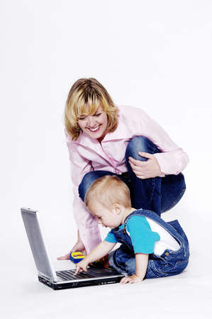 Mother watching her son playing with laptop.