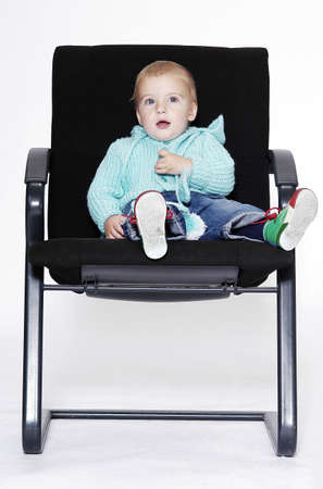 ofis koltuğu: Boy sitting on an office chair.