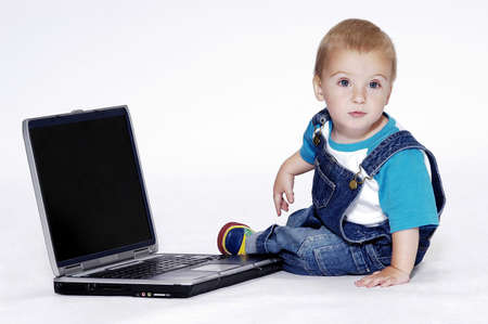 bib overall: Boy playing with laptop.