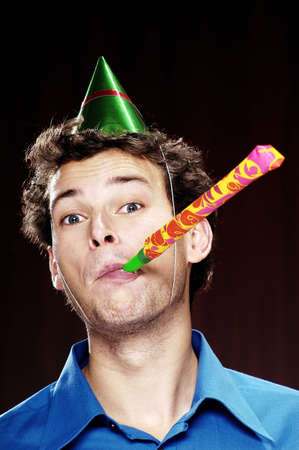 adoration: Man with party hat playing a blowout.