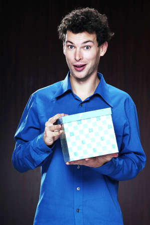 attainment: Man holding a box of present. LANG_EVOIMAGES