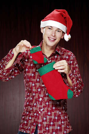 christmas sock: Man in christmas hat holding a christmas sock.