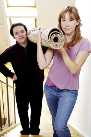 Couple carrying a rolled up carpet to the second floor. Stock Photo - 3192277
