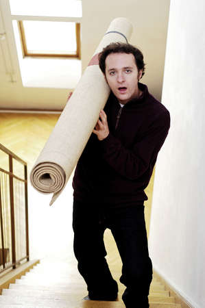 carpet: Man carrying a rolled up carpet to the second floor. LANG_EVOIMAGES