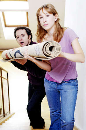 Couple carrying a rolled up carpet to the second floor.
