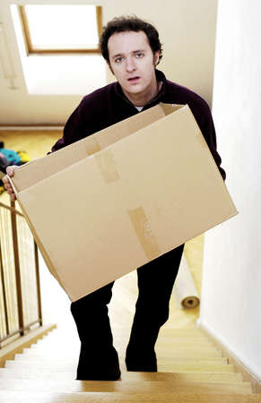 Man carrying a box up the stairs.