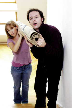 Couple carrying a rolled up carpet to the second floor. Stock Photo - 3192325