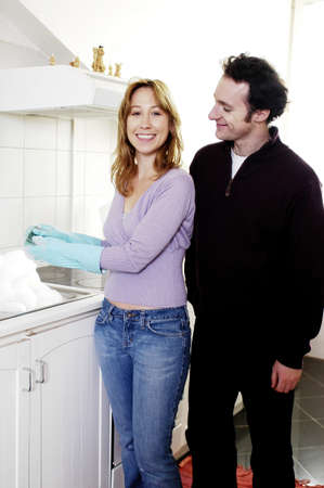Man watching his wife washing dishes. Stock Photo - 3192337