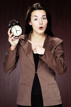 Businesswoman pointing at the alarm clock. Stock Photo - 3192341