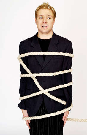kidnapped: Businessman being tied up with rope.