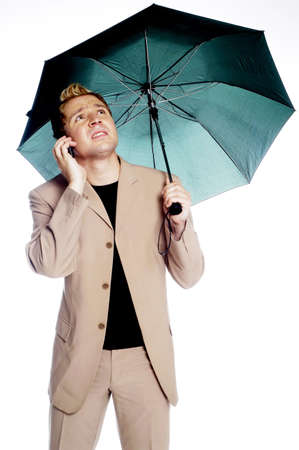 Businessman holding an umbrella while talking on the mobile phone. Stock Photo - 3192352
