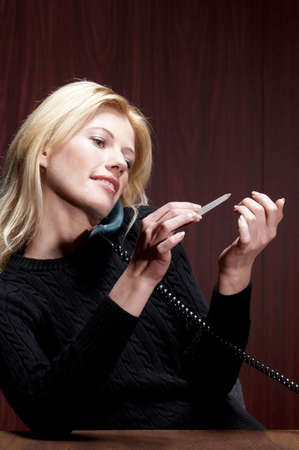 Businesswoman shaping her fingernails while talking on the phone. LANG_EVOIMAGES