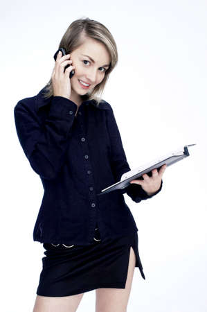 Businesswoman holding a document while talking on the mobile phone. LANG_EVOIMAGES