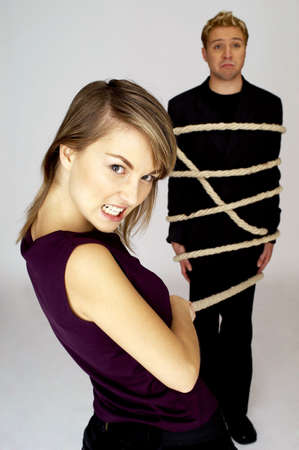 Businessman being tied up by his female colleague. Stock Photo - 3192366