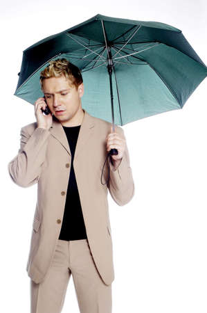 Businessman holding an umbrella while talking on the mobile phone.