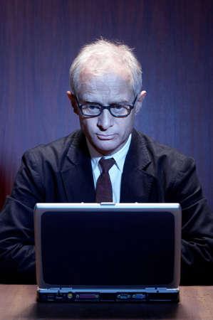 he: Senior businessman using laptop.