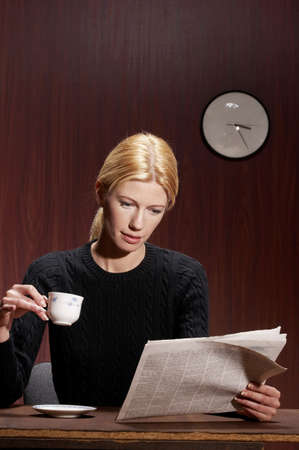 reading newspaper: Businesswoman drinking coffee while reading newspaper.