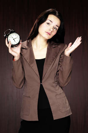 Businesswoman with puzzled look holding an alarm clock. Stock Photo - 3192415