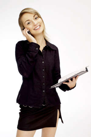 Businesswoman holding a document while talking on the mobile phone. Stock Photo - 3192424
