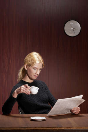 Businesswoman drinking coffee while reading newspaper. Stock Photo - 3192436