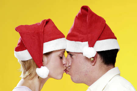 Couple in christmas hats kissing. Stock Photo - 3192450