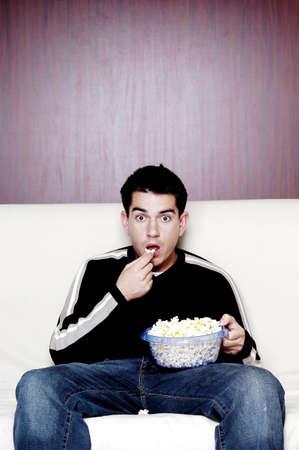 hombre comiendo: Hombre de comer palomitas de ma�z mientras ve la pel�cula.  LANG_EVOIMAGES