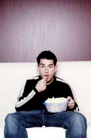 horror movie: Man eating popcorn while watching movie.