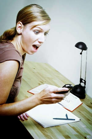 Woman in shock after checking the time on her mobile phone. Stock Photo - 3192492