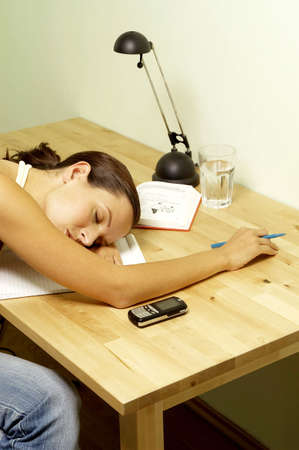 assignment: Woman sleeping while doing her assignment. LANG_EVOIMAGES