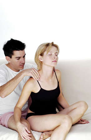 couple on couch: Man giving his girlfriend a shoulder massage.