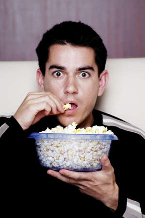watching movie: Man eating popcorn while watching movie.